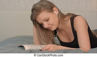 Cute female with headphones reading a magazine while lying on a bed