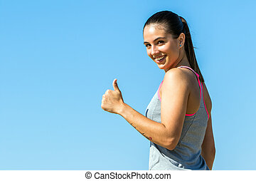 Cute fitness girl doing thumbs up outdoors.