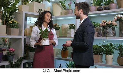 Cute florist offering client to buy potted plant -...