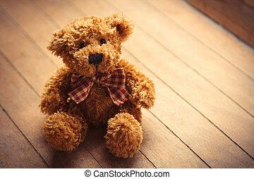 cute fluffy teddy bear on the wonderful brown wooden background
