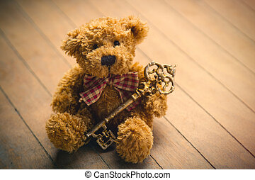 cute fluffy teddy bear with golden key on the wonderful brown wooden background