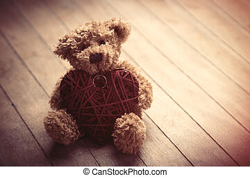 cute fluffy teddy bear with heart shaped toy on the wonderful brown wooden background