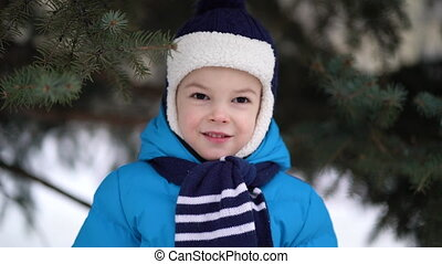 Cute four years old boy portrait on winter forest