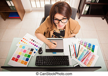 Cute freelance designer at work - Pretty mixed-raced female...