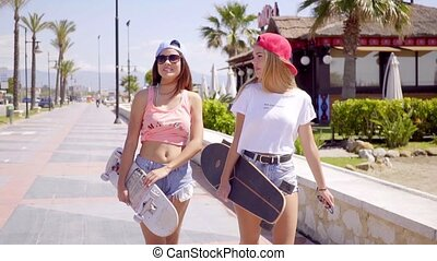 Cute friends in shorts with skateboards
