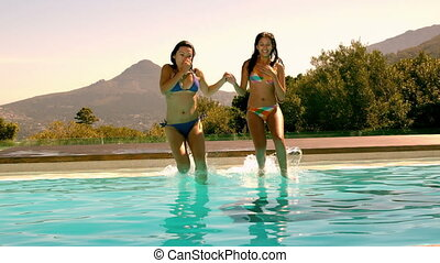 Cute friends jumping into swimming