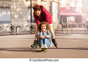 Cute friends with skateboard and skates having fun
