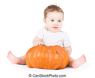 Cute funny baby girl playing with a big pumpkin on white backgro