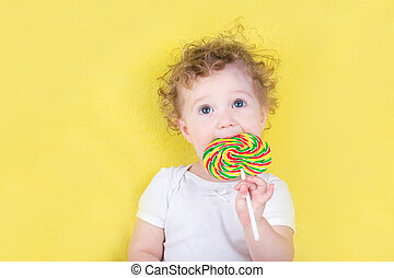 Cute funny baby girl with a big candy on yellow background