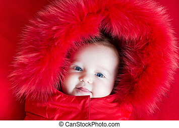 Cute funny baby girl with big blue eyes in a warm winter jacket