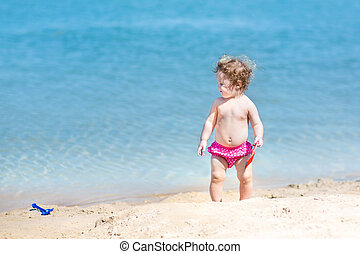 Cute funny baby girl with curly hair playing in sand on a beach