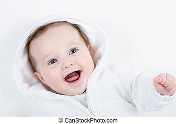 Cute funny baby in a white knitted jacket