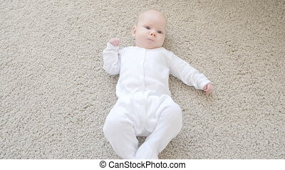 Cute funny baby lying on a beige carpet indoors