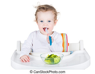 Cute funny baby with big beautiful blue eyes eating broccoli in