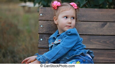 Cute funny beautiful little girl in a jeans jacket sitting on bench in park, smiling and looking at the camera