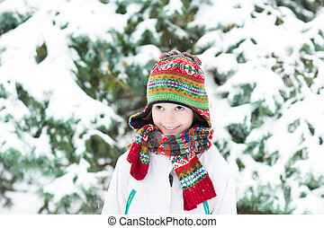 Cute funny child playing in a snowy forest