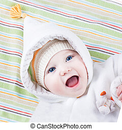 Cute funny laughing baby girl relaxing on a colorful blanket wea
