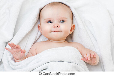 Cute funny smiling baby lying on back in bathing towel