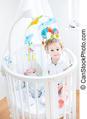 Cute funny toddler girl sitting in a crib of her newborn baby br