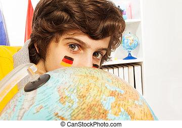 Cute German schoolboy hiding behind the globe