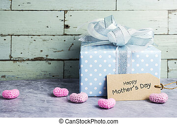 Cute gift box with happy mothers day message on brown paper tag and pink heart