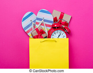 cute gifts, alarm clock and cool sandals in shopping bag and cool laptop on wonderful pink background