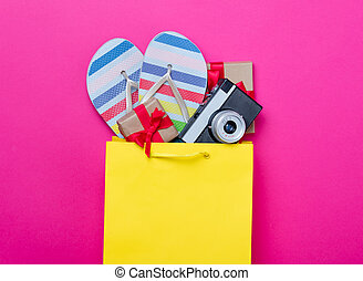 cute gifts, camera and cool sandals in shopping bag and cool laptop on wonderful pink background