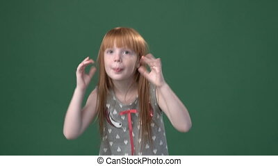 Cute ginger girl playing the ape against chroma key green...