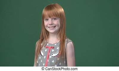 Cute ginger girl smiling against chroma key green screen...