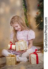 Cute girl among Christmas gifts