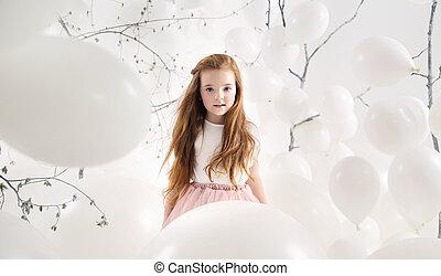 Cute girl among white balloons