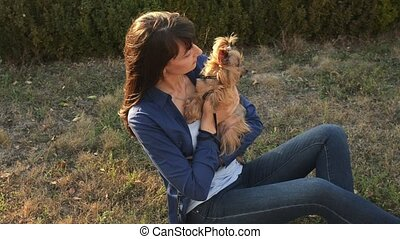 Cute girl and adorable dog Yorkshire terrier sitting outdoors at sunset in the autumn park.