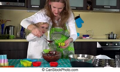 Cute girl and beautiful mother are spooning muffin batter into baking cups