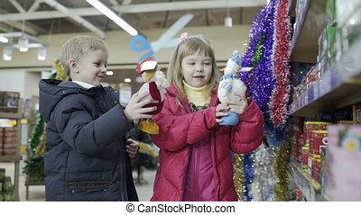 Cute girl and boy playing with christmas toys at shopping...