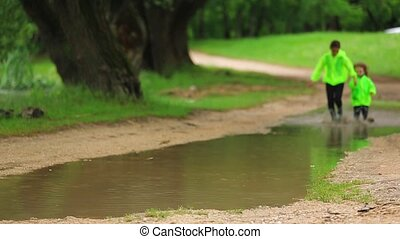 Cute Girl And Boy Running In Huge Puddle