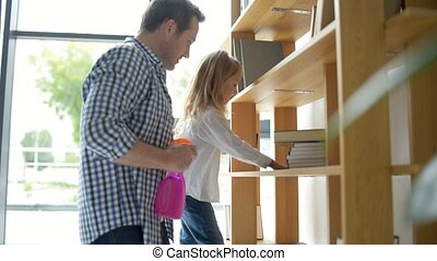 Cute girl and her father cleaning the flat