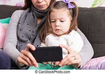 Cute Girl And Mom Watching Cartoon On Mobile Phone