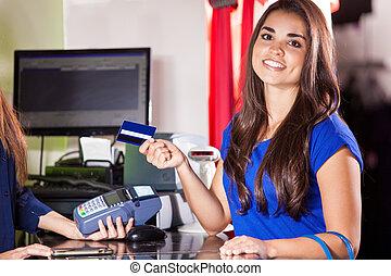 Cute girl at a cash register - Beautiful Hispanic woman...