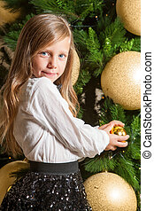 Cute girl at home with christmas tree.