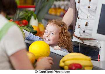 Cute girl at the checkout counter - Image of a cute girl at...