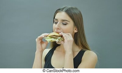 cute girl biting hamburger on black background