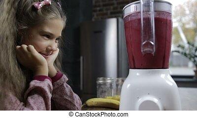 Cute girl blending fresh berry smoothie in blender -...