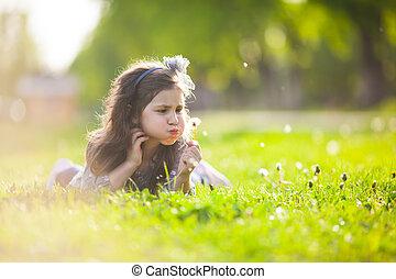 Cute girl blowing dandelion