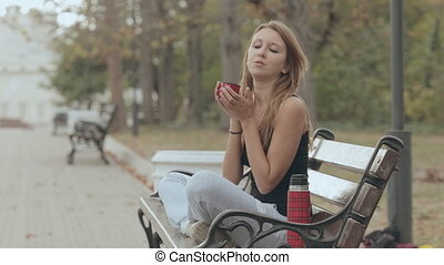Cute girl blowing on hot tea from a thermos and drink it,...