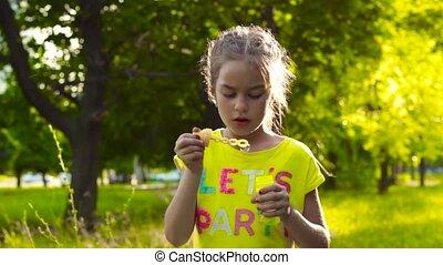 Cute girl blowing soap bubbles in park - Pretty cute little...