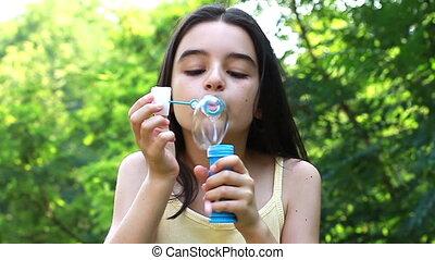 Cute girl blowing soap bubbles