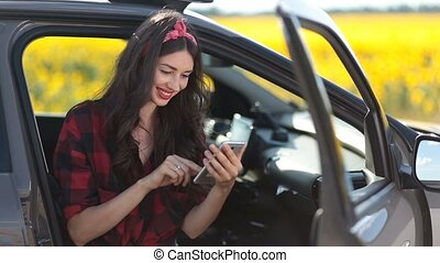 Cute girl browsing the net with smartphone in car -...
