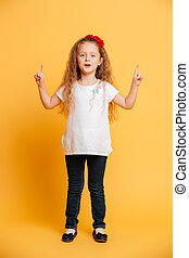 Cute girl child standing isolated pointing
