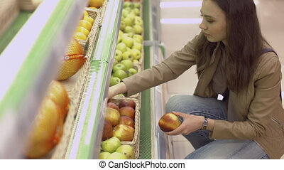 Cute girl chooses fresh apples at the supermarket