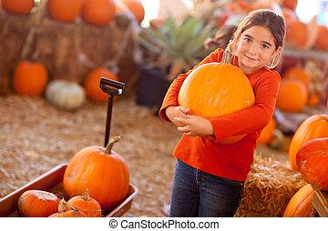 Cute Girl Choosing A Pumpkin